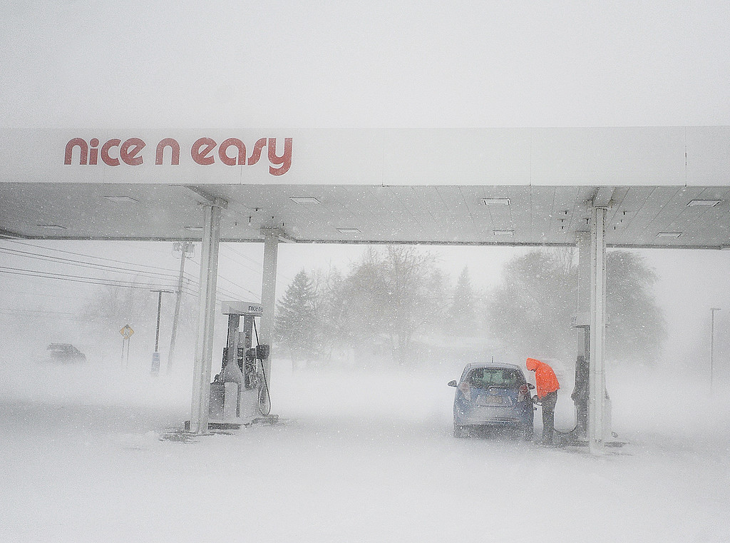 . In a Tuesday, Nov. 18, 2014 photo, a man fill up in white out conditions at a gas station on Route New York State Route 12F near Brownville, N.Y. A ferocious lake-effect storm left the Buffalo area buried under 6 feet of snow, trapping people on highways and in homes, and another storm expected to drop 2 to 3 feet more was on its way. (AP Photo/The Watertown Daily Times, Justin Sorensen)
