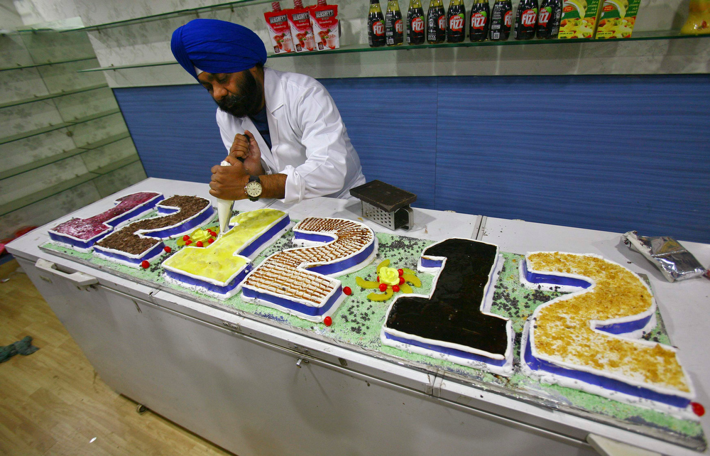 ". A man applies the finishing touches to a cake which reads, ""12.12.12\"" at a shop in Panchkula, in the northern Indian state of Haryana December 12, 2012. REUTERS/Ajay Verma"