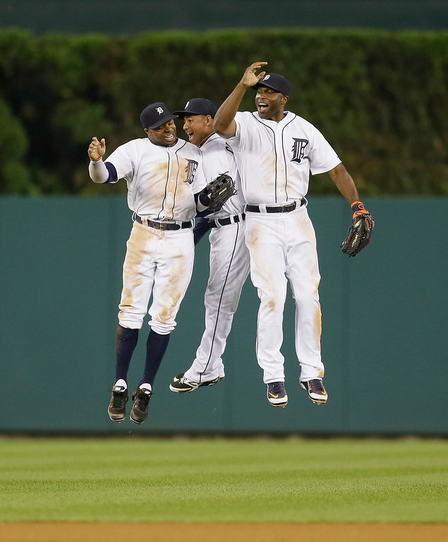 . Detroit Tigers center fielder Rajai Davis, left, left fielder Ezequiel Carrera, center and right fielder Torii Hunter celebrate the Tigers\'w 4-2 win over the Colorado Rockies in an interleague baseball game, Friday, Aug. 1, 2014, in Detroit. (AP Photo/Carlos Osorio)