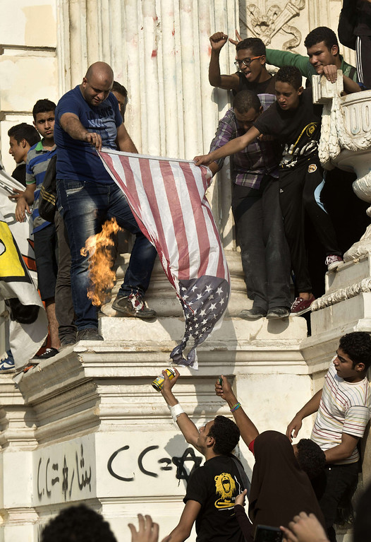 . Supporters of Egyptian ousted president Mohamed Morsi and of the Muslim brotherhood movement burn an American flag during a rally outside of the presidential palace in Cairo on October 11, 2013. An Islamist alliance urged its supporters to stay away from Cairo\'s Tahrir Square during protests to avoid more bloodshed after a week in which nearly 80 Egyptians were killed.  KHALED DESOUKI/AFP/Getty Images