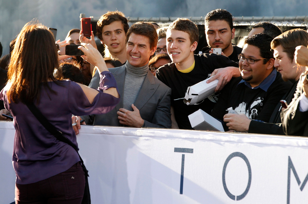 """. Actor Tom Cruise poses with fans along Hollywood Boulevard at the premiere of his new film \""""Oblivion\"""" in Hollywood April 10, 2013.    REUTERS/Fred Prouser"""