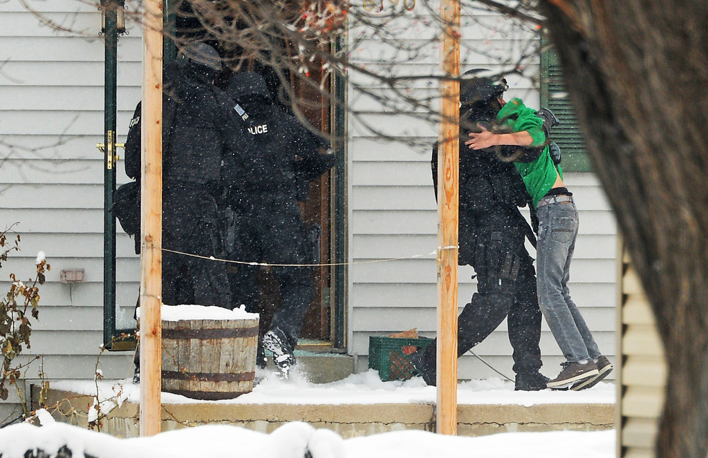 . A member of the SWAT brings out a hostage as they rush into a house in Arvada, February, 04 2014. There is heavy police and SWAT presence in the 6100 block of Grey Street, and surrounding homes have been evacuated. (Photo by RJ Sangosti/The Denver Post)
