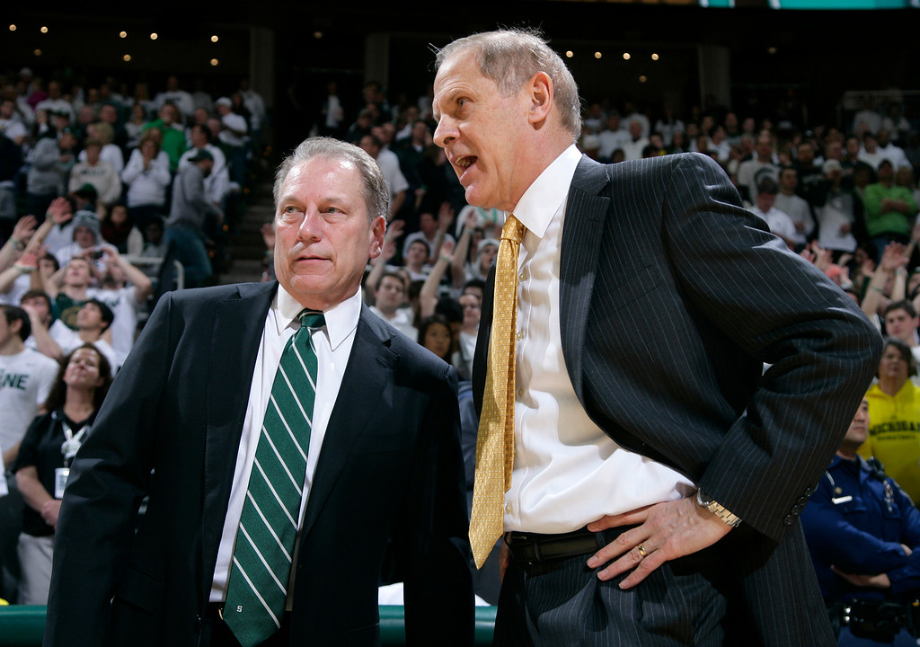 . Michigan State coach Tom Izzo, left, and Michigan coach John Beilein talk before an NCAA college basketball game, Sunday, Feb. 1, 2015, in East Lansing, Mich. Michigan State won 76-66 in overtime. (AP Photo/Al Goldis)