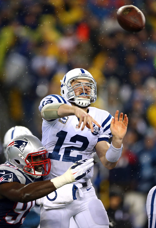 . FOXBORO, MA - JANUARY 11:  Andrew Luck #12 of the Indianapolis Colts throws a pass against the New England Patriots during the AFC Divisional Playoff game at Gillette Stadium on January 11, 2014 in Foxboro, Massachusetts.  (Photo by Elsa/Getty Images)