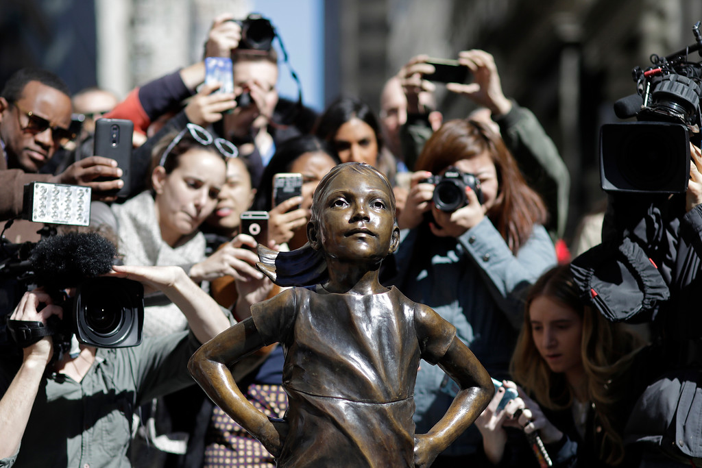 ". People stop to photograph the ""Fearless Girl\"" statue, Wednesday, March 8, 2017, in New York. The statue was installed by investment firm State Street Global Advisors. An inscription at the base reads, \""Know the power of women in leadership. She makes a difference.\"" (AP Photo/Mark Lennihan)"