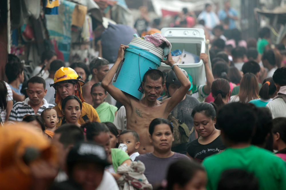 . Residents carry back their belongings as they return to their homes after a fire broke out at a slum area in Pasay, south of Manila, Philippines on Wednesday, July 24, 2013. Pasay City Fire Marshall Major Douglas Guiyab said about 250 houses were gutted in the area and the cause of the fire is still being determined. (AP Photo/Aaron Favila)