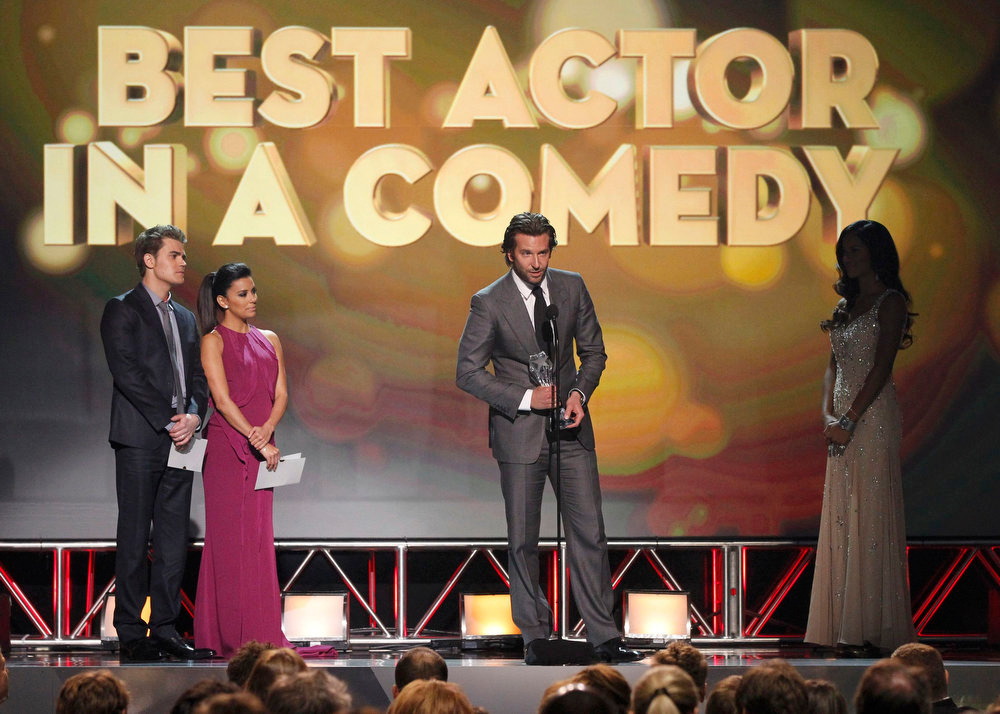 ". Presenters Paul Wesley and Eva Longoria (L) look on as Bradley Cooper accepts the award for ""Best Actor in a Comedy Movie\"" for \""Silver Linings Playbook\"" at the 2013 Critics\' Choice Awards in Santa Monica, California, January 10, 2013.     REUTERS/Mario Anzuoni"