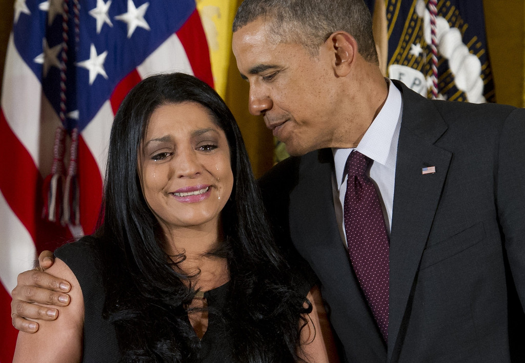 . US President Barack Obama stands alongside Lenora Alvarado  as he awards a Medal of Honor to her late father Army Specialist Four Leonard Alvarado during a ceremony in the East Room of the White House in Washington on March 18, 2014.   AFP PHOTO / Saul LOEB/AFP/Getty Images