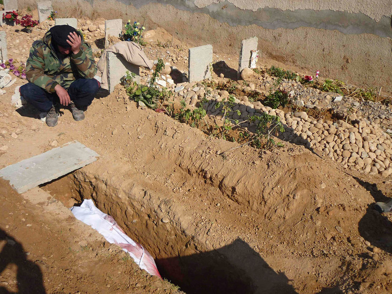 . A Free Syrian Army fighter mourns near the grave of his comrade who died in what the Free Syrian Army said were clashes with forces loyal to Syria\'s President Bashar al-Assad in Qusair town near Homs March 25, 2013. Picture taken March 25, 2013. REUTERS/Trad al-Zouhouri//Shaam News Network/Handout