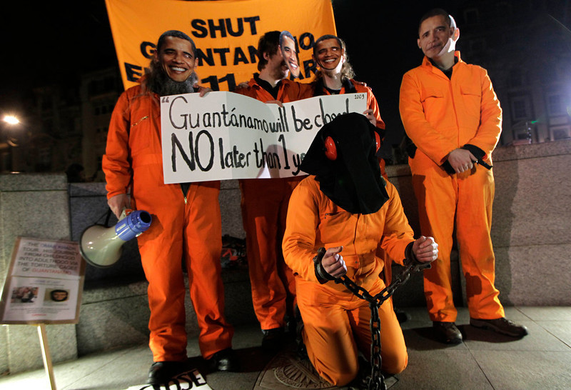 . Campaigners gather outside the U.S. Embassy in London, holding various signs against the prison and some wearing US President Obama masks, to mark the 11th anniversary of the opening of Guantanamo Bay U.S. prison in eastern Cuba, Friday, Jan. 11, 2013. (AP Photo/Sang Tan)