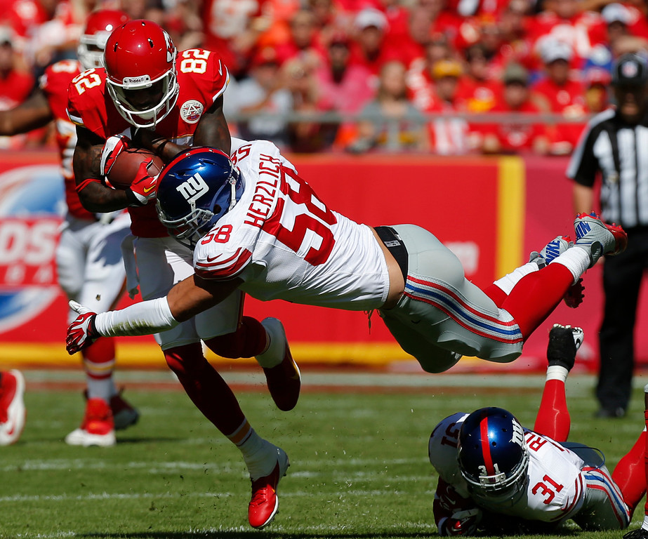 . Kansas City Chiefs wide receiver Dwayne Bowe (82) is tackled by New York Giants middle linebacker Mark Herzlich (58) during the first half of an NFL football game at Arrowhead Stadium in Kansas City, Mo., Sunday, Sept. 29, 2013. (AP Photo/Ed Zurga)