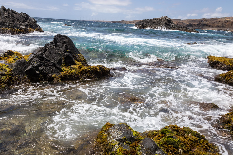 Rocks line the beach and are interspersed in the water on part of the Aruba coastline.