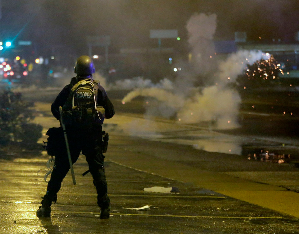 . A law enforcement officer watches Sunday, Aug. 17, 2014, as tear gas is fired to disperse a crowd protesting the shooting of teenager Michael Brown last Saturday in Ferguson, Mo. Brown\'s shooting in the middle of a street following a suspected robbery of a box of cigars from a nearby market has sparked a week of protests, riots and looting in the St. Louis suburb. (AP Photo/Charlie Riedel)