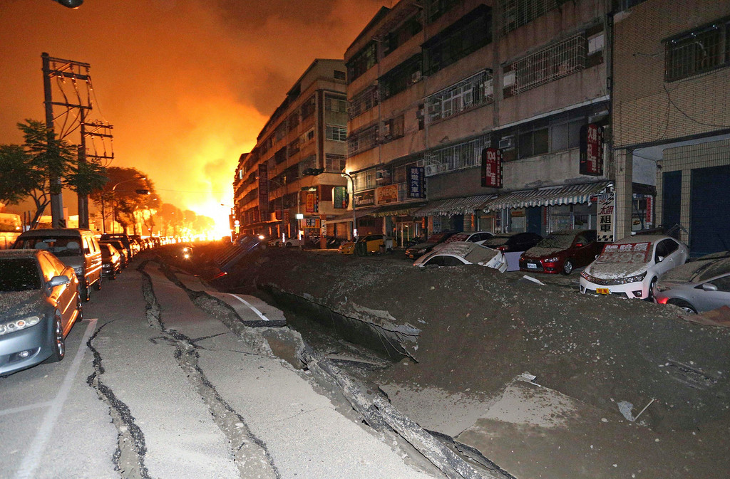 . Tossed vehicles line an destroyed street as flames continue to burn from multiple explosions from an underground gas leak in Kaohsiung, Taiwan, early Friday, Aug. 1, 2014.  A massive gas leakage early Friday caused five explosions that killed several people and injured over 200 in the southern Taiwan port city of Kaohsiung. (AP Photo)