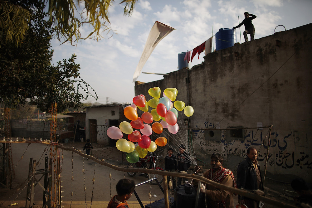 . A Pakistani vendor sells balloons in a Christian neighborhood for the Christmas holidays in Islamabad, Pakistan on Monday, Dec. 24, 2012. (AP Photo/Nathalie Bardou)