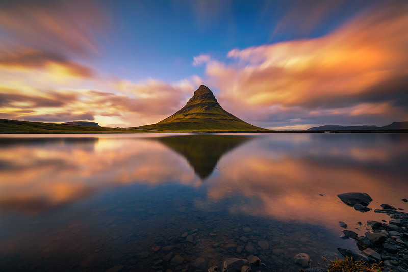 Sunset over Kirkjufell mountain with reflection in a nearby lake in Iceland