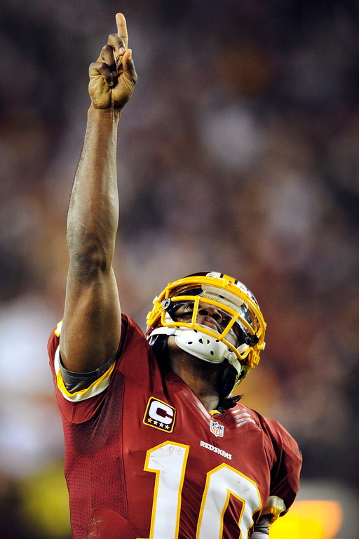 . Washington Redskins quarterback Robert Griffin III points skyward after throwing a touchdown pass to wide receiver Pierre Garcon during the second half of an NFL football game against the New York Giants in Landover, Md., Monday, Dec. 3, 2012. (AP Photo/Nick Wass)