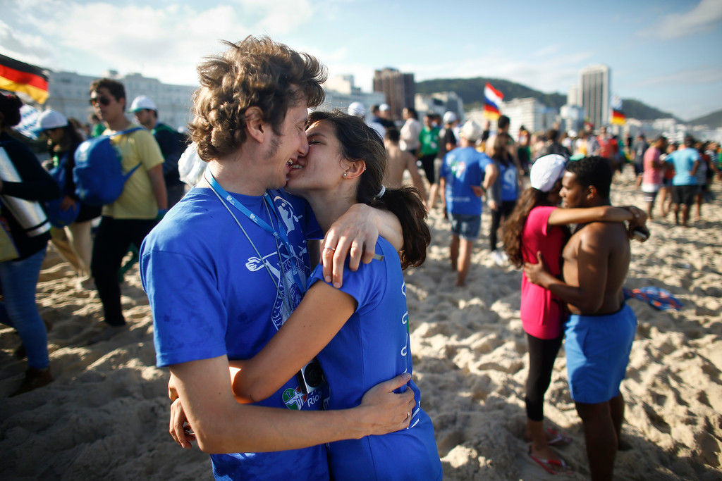. Pilgrims kiss on Copacabana beach as they wait for Pope Francis\' arrival in Rio de Janeiro, Brazil, Saturday, July 27, 2013. Francis will preside over an evening vigil service on Copacabana beach that is expected to draw more than 1 million young people. (AP Photo/Victor R. Caivano)