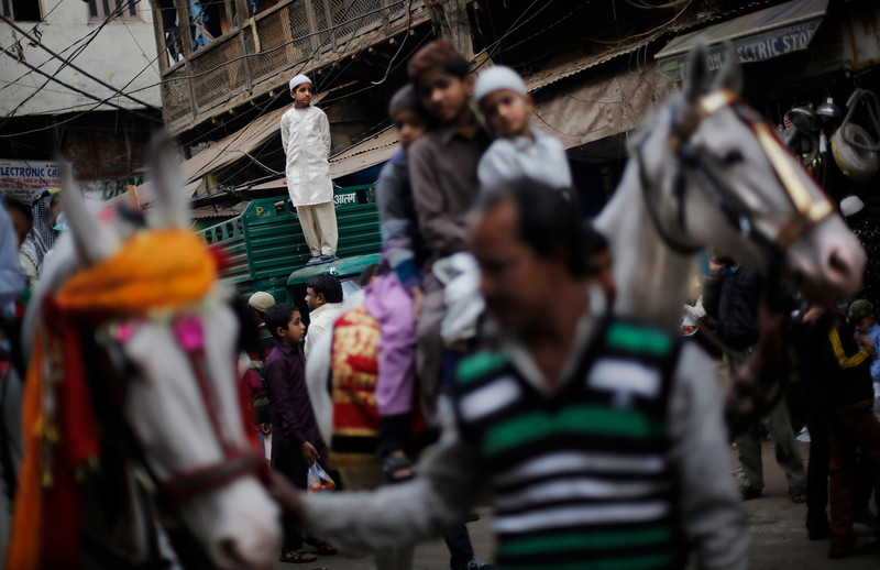 . An Indian Muslim boy stands on the roof of an auto rickshaw as he watches the procession to mark the birth anniversary of Prophet Muhammad in New Delhi, India, Tuesday, Jan. 14, 2014. (AP Photo/Altaf Qadri)