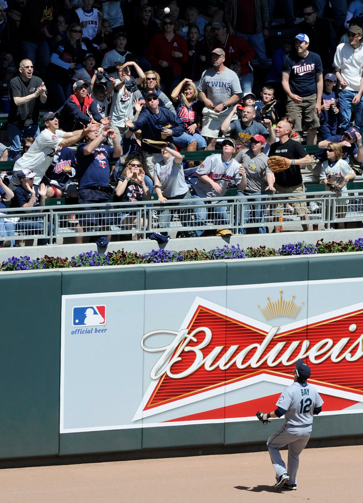 . Seattle left fielder Jason Bay looks up as fans reach for the home run ball hit by Minnesota\'s Chris Herrmann during the fourth inning. (Photo by Hannah Foslien/Getty Images)