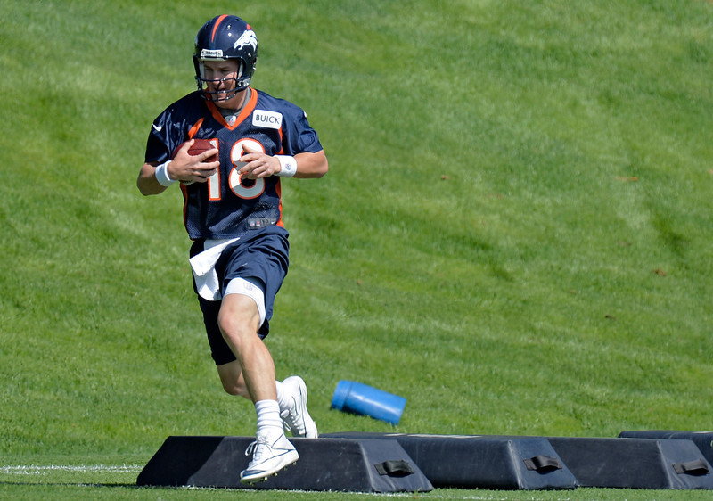 . Peyton Manning (18) of the Denver Broncos runs through drills during the teams OTAs May 20, 2013 at Dove Valley. All offseason training activities (OTAs) are voluntary until the mandatory minicamp June 11-13. (Photo By John Leyba/The Denver Post)