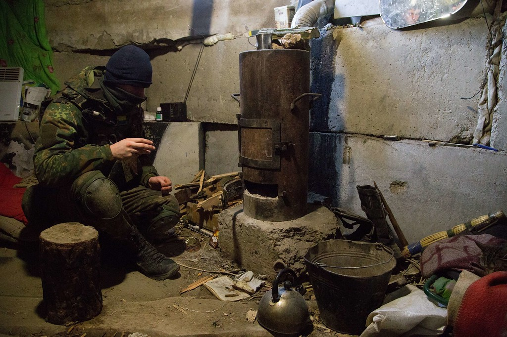 """. A Ukrainian serviceman sits near a stove in a dugout at a position near the village of Peski, Donetsk region, on February 18, 2015. Ukrainian troops pulled out of the hotspot eastern town of Debaltseve after it was stormed by pro-Russian rebels in what the EU said was a \""""clear violation\"""" of an internationally-backed truce. OLEKSANDR RATUSHNIAK/AFP/Getty Images"""