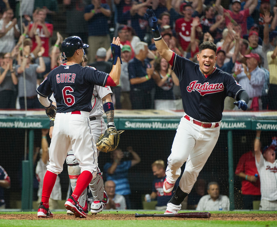 . Cleveland Indians\' Brandon Guyer (6) is congratulated by teammate Giovanny Urshela after scoring the winning run against the Boston Red Sox in the ninth inning of a baseball game in Cleveland, Monday Aug. 21, 2017. (AP Photo/Phil Long)