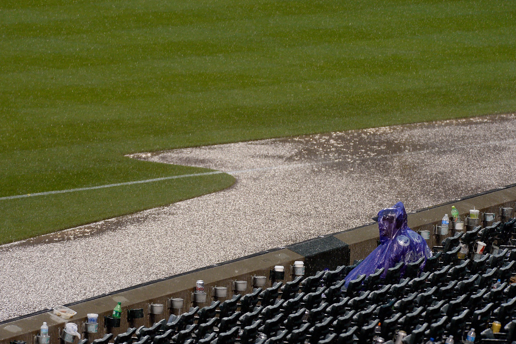 . DENVER, CO - MAY 22: Rockies fans brave the rain as they sit in their seat watching the grounds crew roll out the tarp during a second rain delay at the Colorado Rockies San Francisco Giants game May 22, 2014 at Coors Field. (Photo by John Leyba/The Denver Post)