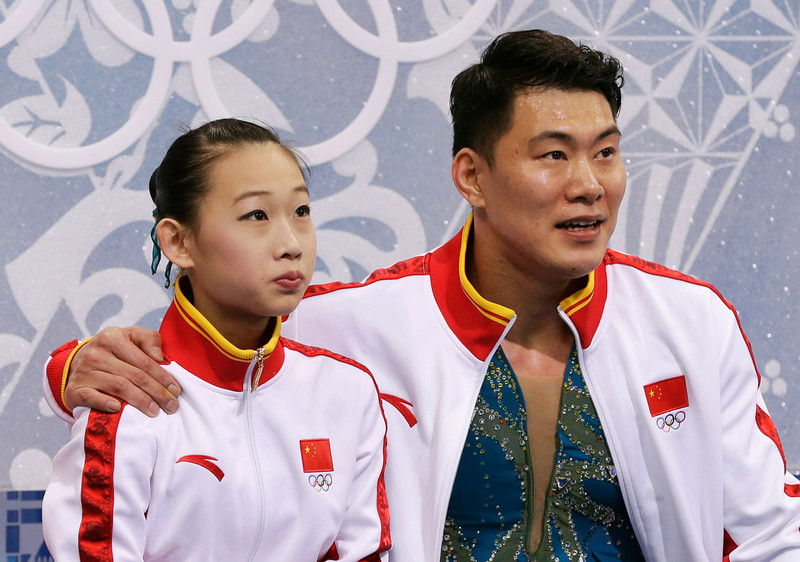 . Peng Cheng and Zhang Hao of China wait in the results area after competing in the pairs free skate figure skating competition at the Iceberg Skating Palace during the 2014 Winter Olympics, Wednesday, Feb. 12, 2014, in Sochi, Russia. (AP Photo/Darron Cummings)
