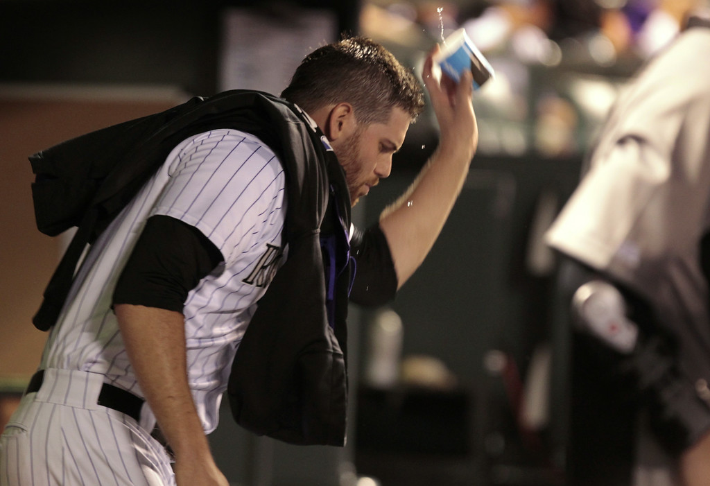 . Colorado Rockies relief pitcher Adam Ottavino throws a cup of water in the dugout after leaving the baseball game against the Chicago Cubs in the 11th inning in Denver on Tuesday, Aug. 5, 2014. (AP Photo/Joe Mahoney)