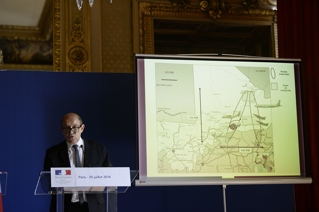 . French Defense minister Jean-Yves Le Drian delivers a press conference at the Elysee Palace on June 25, 2014 with behind him an image released by ECPAD showing the location of the crash of the Air Algerie flight AH5017 in Mali\'s Gossi region, west of Gao. The first images of the Air Algerie crash site in Mali emerged on July 25, showing a stark terrain littered with bits of a plane that appears to have been pulverised on impact. France announced there were no survivors among the 118 people on board the Air Algerie flight that crashed over Mali the day before, saying bad weather was the likely cause of the disaster. AFP PHOTO / STEPHANE DE SAKUTINSTEPHANE DE SAKUTIN/AFP/Getty Images