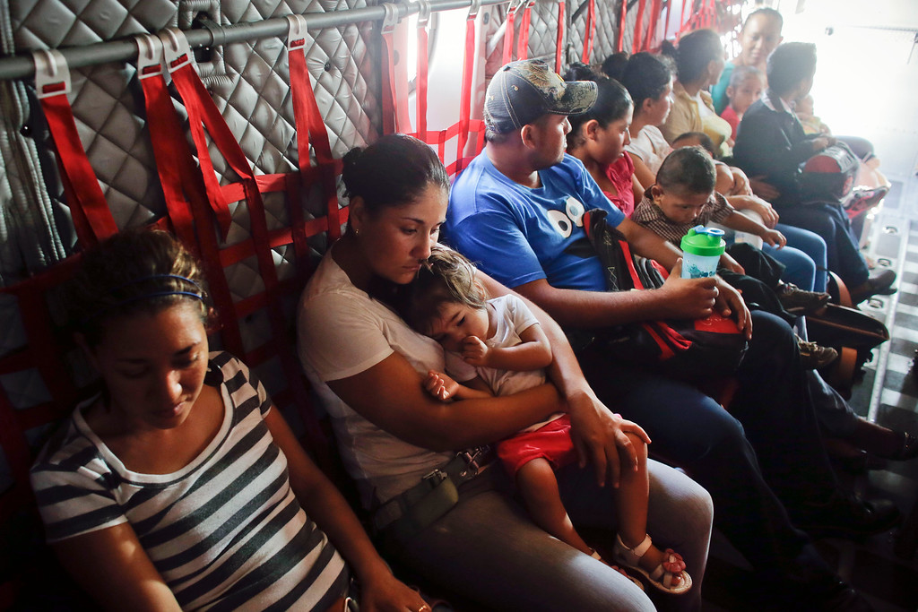 . Vanesa Torres, from Mexico, center, holds her one-year-old baby Arantxa as they wait to be evacuated with about 50 tourists and locals aboard Mexican air force cargo plane to Mexico City from Los Cabos, Mexico, Thursday, Sept. 18, 2014. Mexican authorities said 8,000 people, including tourists and locals anxious to leave, would be airlifted out on Thursday from Los Cabos following the blow from Hurricane Odile. (AP Photo/Victor R. Caivano)