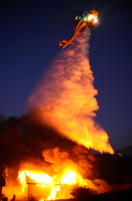 . A fire helicopter makes a water drop on a fully involved garage fire at the Silver Fire near Banning, California August 7, 2013.  Hundreds of residents of three small communities in the high desert east of Los Angeles were evacuated on Wednesday as an out-of-control wildfire headed toward them.    Photo by Gene Blevins/LA Daily News