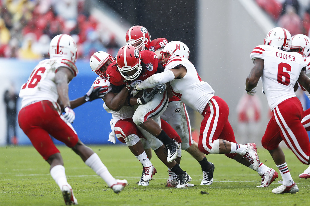 . Todd Gurley #3 of the Georgia Bulldogs is tackled by a group of Nebraska Cornhuskers defenders in the first half during the TaxSlayer.com Gator Bowl at Everbank Field on January 1, 2014 in Jacksonville, Florida. (Photo by Joe Robbins/Getty Images)