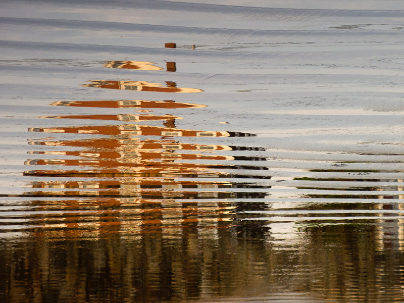 A stately beach shack catching the morning light, reflected in the wet sand, at low tide.