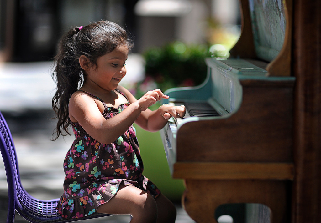 . Vacationing with her family from Nashville, Tenn., Kairi Ramirez, 3, plays the piano on Denver\'s 16th Street Mall on a sunny Monday afternoon, July 5, 2010.   (Diego James Robles, The Denver Post)