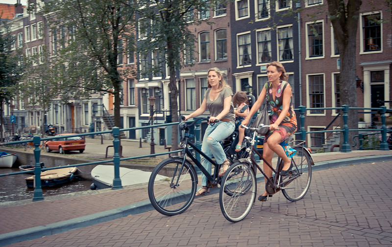 Two women and a child on bikes in Amsterdam