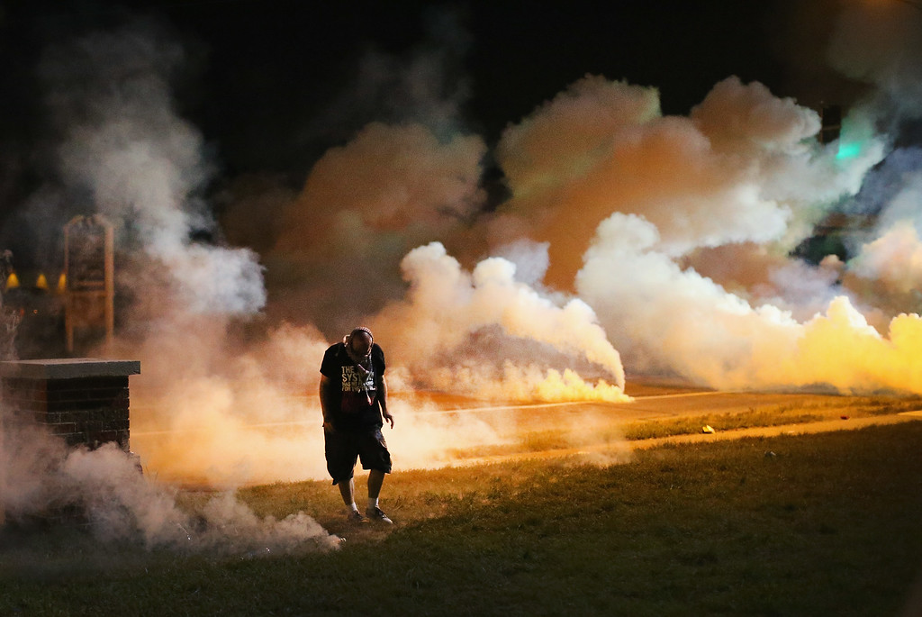 . Demonstrators, protesting the shooting death of teenager Michael Brown, flee as police shoot tear gas into the crowd of several hundred after someone reportedly threw a bottle at the line of police on August 13, 2014 in Ferguson, Missouri. Brown was shot and killed by a Ferguson police officer on Saturday. Ferguson, a St. Louis suburb, is experiencing its fourth day of violent protests since the killing.  (Photo by Scott Olson/Getty Images)