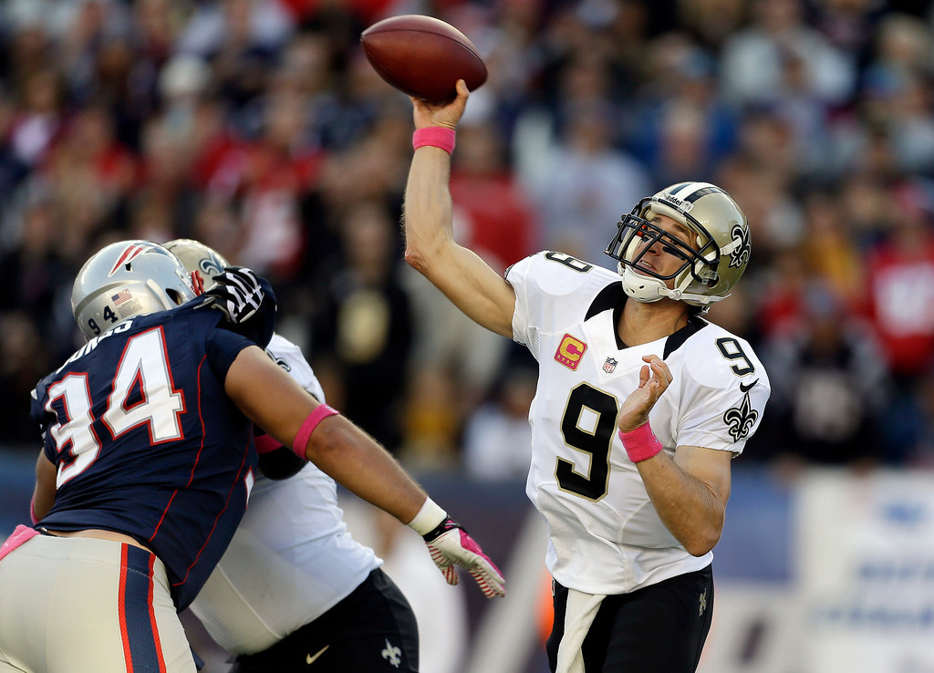 . New Orleans Saints quarterback Drew Brees (9) passes over New England Patriots defensive tackle Chris Jones (94) in the first quarter of an NFL football game Sunday, Oct.13, 2013, in Foxborough, Mass. (AP Photo/Steven Senne)