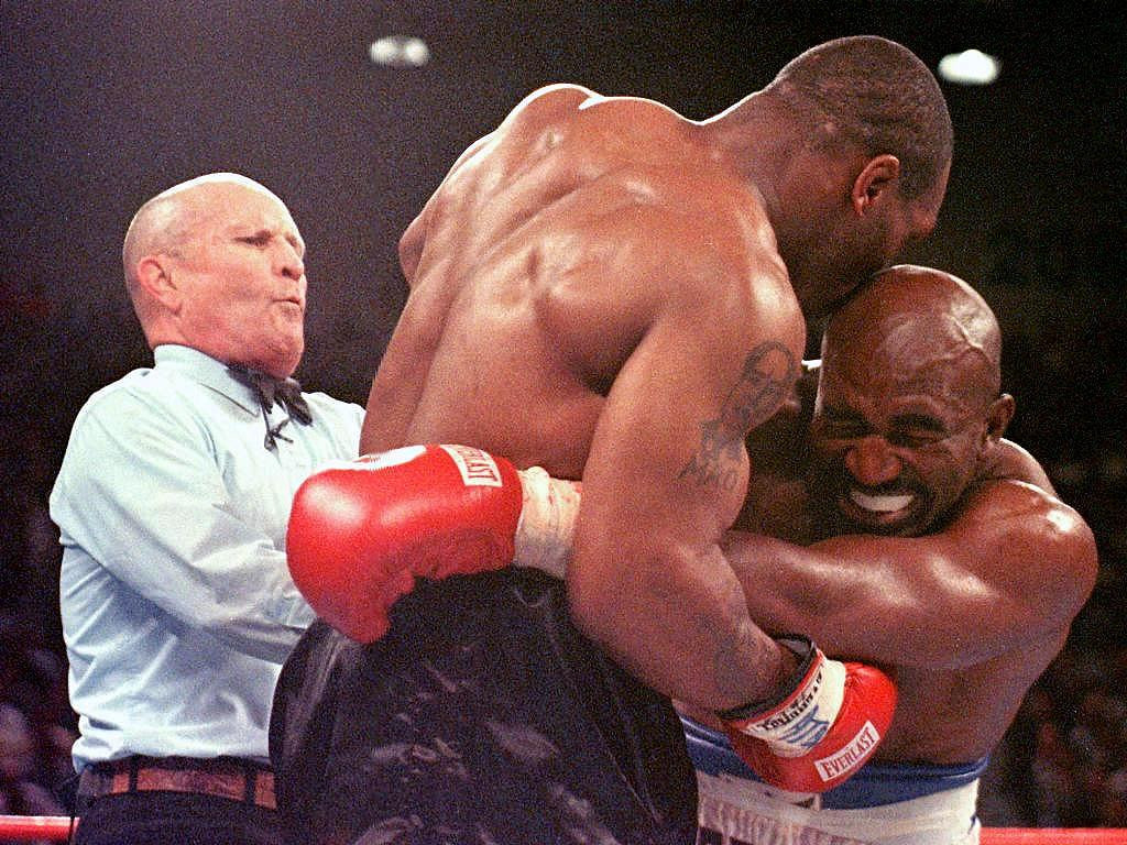 ". (FILES): This 28 June 1997 file photo shows referee Lane Mills (L) stepping in as Evander Holyfield (R) reacts after Mike Tyson (C) bit his ear in the third round of their WBA Heavyweight Championship Fight at the MGM Grand Garden Arena in Las Vegas, NV.  A decade after his infamous ""Bite Fight\"" victory over Mike, Holyfield still dreams of retaking boxing\'s heavyweight throne and considers most reigning champions \""beatable\"". The 44-year-old US veteran will fight 41-year-old American Lou Savarese in a 10-round affair 30 June 2007 in El Paso, Texas, seeking the fourth victory in a row since making a comeback after being banished by New York officials following a loss.    (JEFF HAYNES/AFP/Getty Images)"