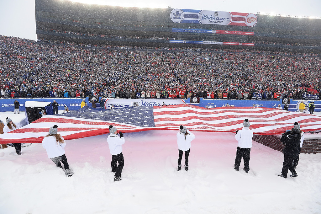 . A giant American flag is unfurled during the U.S. National Anthem before the Toronto Maple Leafs play the Detroit Red Wings during the 2014 Bridgestone NHL Winter Classic on January 1, 2014 at Michigan Stadium in Ann Arbor, Michigan.  (Photo by Jamie Sabau/Getty Images)