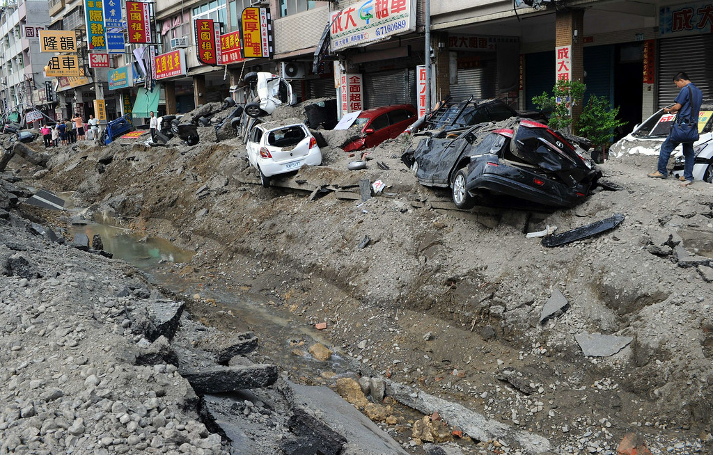 . Local residents walk past the explosion site in southern Kaohsiung city on August 1, 2014.  A series of powerful gas blasts killed at least 24 people and injured 271 in the southern Taiwanese city of Kaohsiung, overturning cars and ripping open roads, officials said.   AFP PHOTO / SAM YEH/AFP/Getty Images