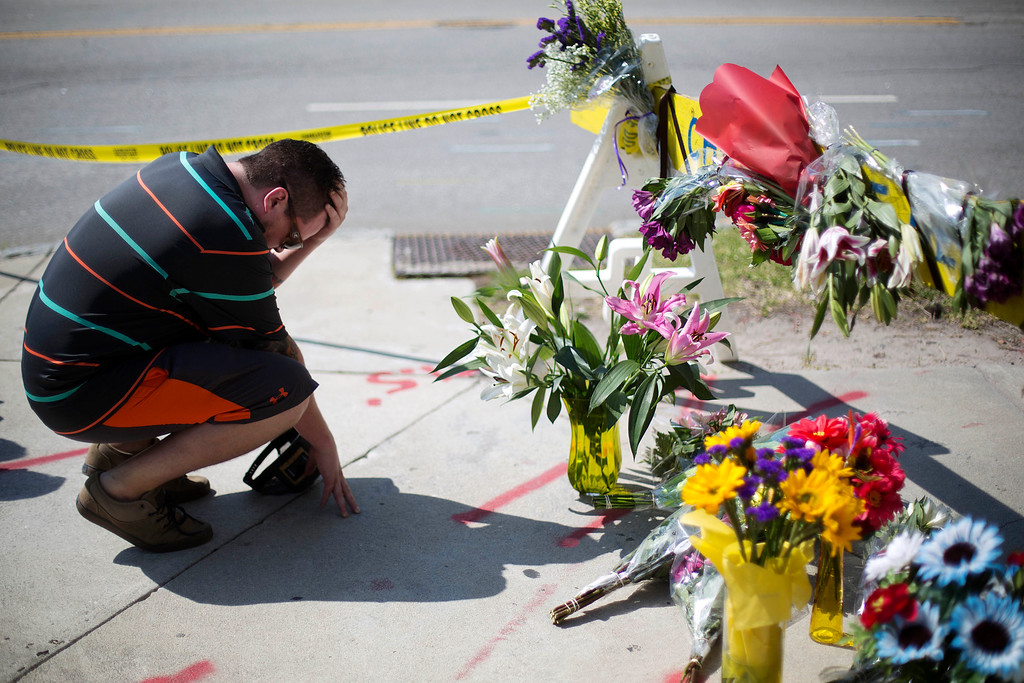 . Noah Nicolaisen, of Charleston, S.C., kneels at a makeshift memorial down the street from where a white man opened fire Wednesday night during a prayer meeting inside the Emanuel AME Church killing several people in Charleston, Thursday, June 18, 2015. (AP Photo/David Goldman)