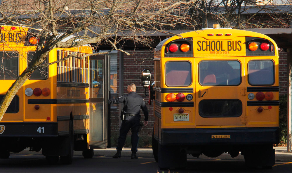 . A police officer speaks with a school bus driver at the entrance of Marlboro Elementary School at Marlboro Township in New Jersey, January 3, 2013. The New Jersey town of Marlboro places armed guards in all of its schools in the wake of deadly Connecticut school shooting which killed 26 people, including 20 school children. REUTERS/Eduardo Munoz