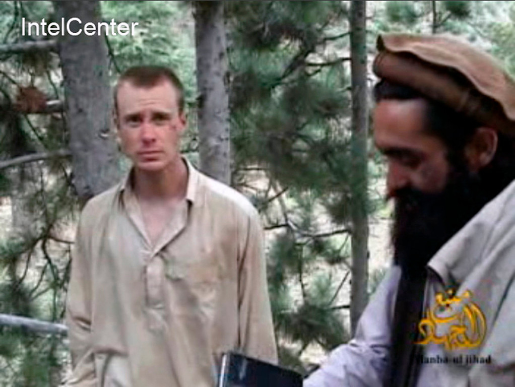 . FILE - This file image provided by IntelCenter on Dec. 8, 2010, shows a frame grab from a video released by the Taliban containing footage of a man believed to be Bowe Bergdahl, left.  Saturday, May 31, 2014, U.S. officials say Bergdahl, the only American soldier held prisoner in Afghanistan has been freed and is in U.S. custody. The officials say his release was part of a negotiation that includes the release of five Afghan detainees held in the U.S. prison at Guantanamo Bay, Cuba. (AP Photo/IntelCenter, File)