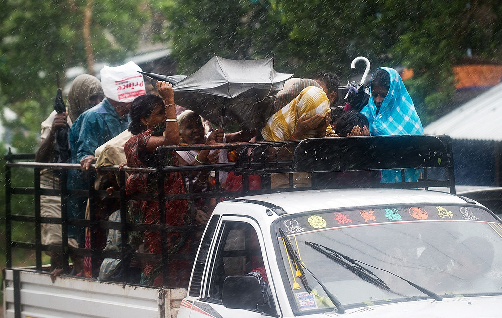 . Indian villagers try to cover themselves from heavy rainfall and strong winds as they ride a pickup truck  in Srikakulam district on October 12, 2013. India evacuated nearly half a million people as massive cyclone Phailin closed in on the impoverished east coast, with winds already uprooting trees and tearing into the flimsy homes.  MANAN VATSYAYANA/AFP/Getty Images