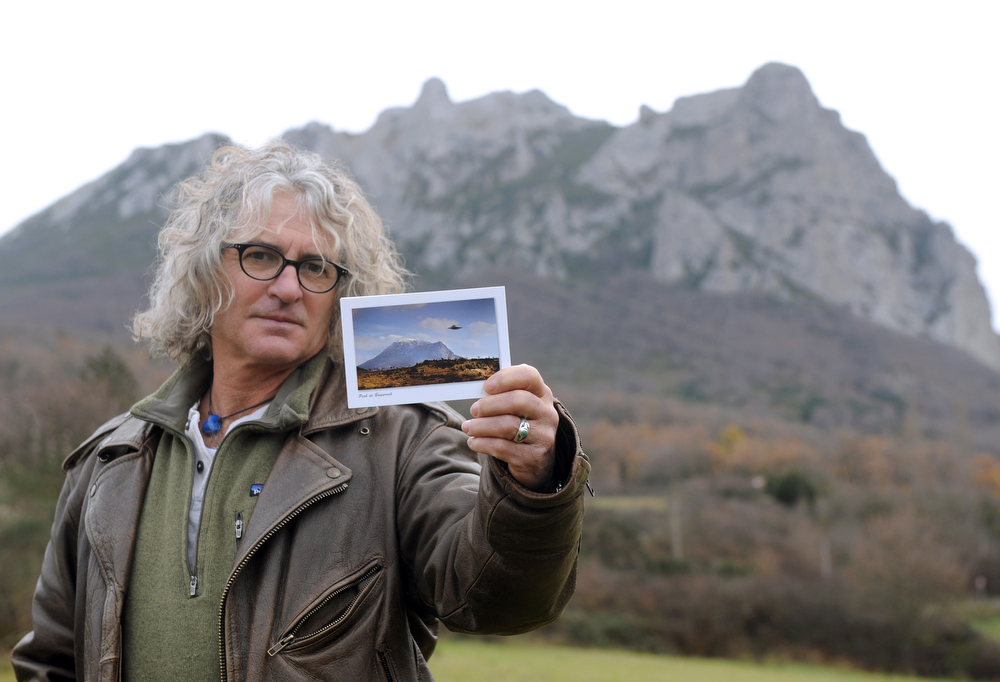 Description of . French photographer Jean-Louis Socquet-Juglard shows, on December 19, 2012 in the southwestern village of Bugarach,  the postcard he created, a combo of a flying saucer above the Bugarach peak. The 1,231 meter high peak of Bugarach is one of the few places on Earth some say will be spared when the world reportedly ends on December 21, the end of an era that lasted over 5,000 years, according to the Mayan