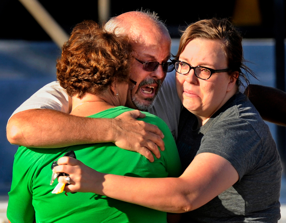 . Tom Sullivan, center, hugs his wife Terry, left, and daughter Megan outside Gateway High School, Friday July 20, 2012, in Aurora. Sullivan was still missing his son, who he said was at the movies in the the Century 16 theater where about 50 people were shot 12 fatally early Friday in Aurora. RJ Sangosti, The Denver Post