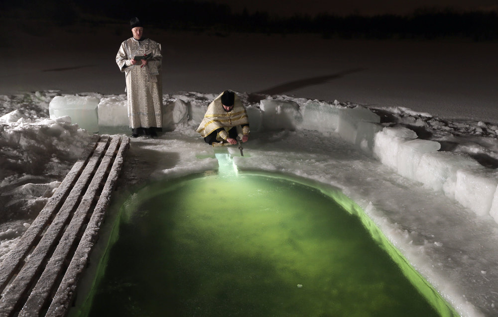 Description of . An Orthodox priests conduct a service at the ice hole of a lake on the eve of Russian Orthodox Epiphany in Minsk, Belarus, late Friday, Jan. 18, 2013. Orthodox Church believers celebrate Epiphany on Jan. 19. (AP Photo/Sergei Grits)