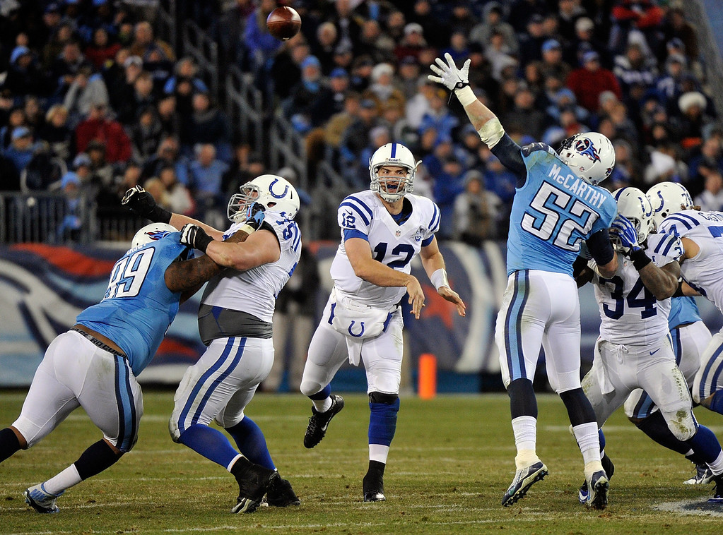 . NASHVILLE, TN - NOVEMBER 14:  Quarterback Andrew Luck #12 of the Indianapolis Colts throws a pass over the outstretched arm of Colin McCarthy #52 of the Tennessee Titans at LP Field on November 14, 2013 in Nashville, Tennessee.  (Photo by Frederick Breedon/Getty Images)